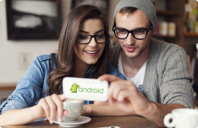 парень и девушка смотрят на телефон андроид