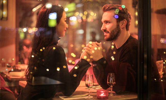 свидание с девушкой в ресторане, держит ее руки
